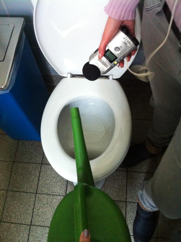 Gießkanne und Aufnahmegerät über der Toilette