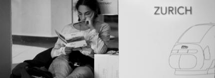 junge Frau liest am Bahnhof