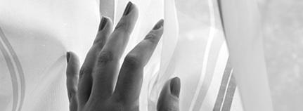 Hand am Fenstervorhang